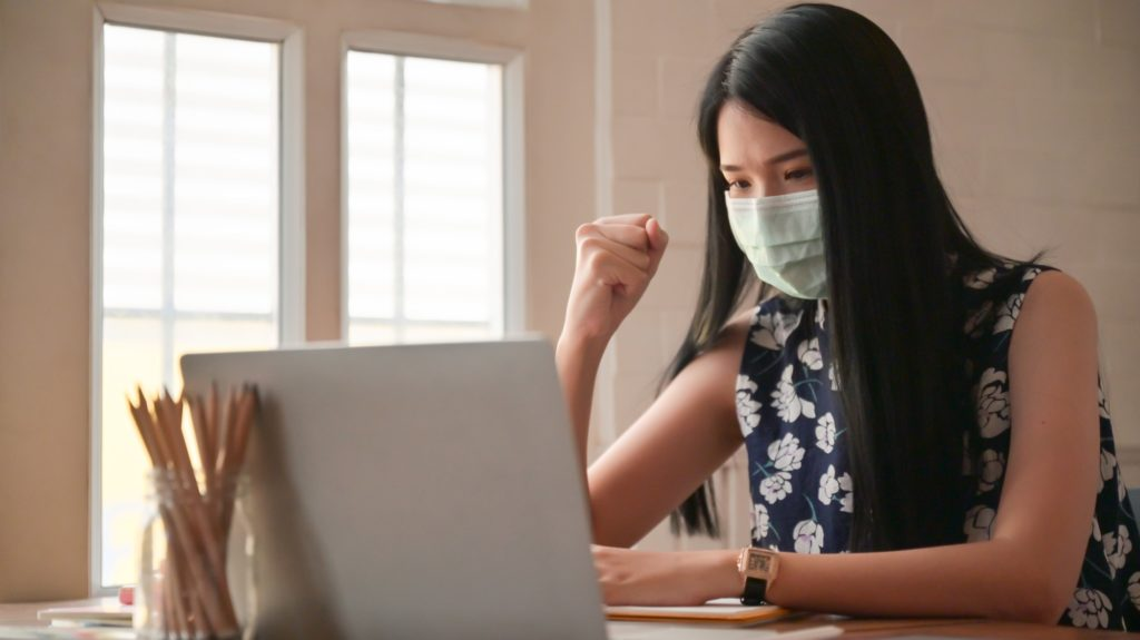 Girl wearing a mask with confident gestures.She works at home to protect against the Covid-19 virus.