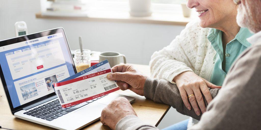 Senior Adult Holding Ticket Laptop Concept